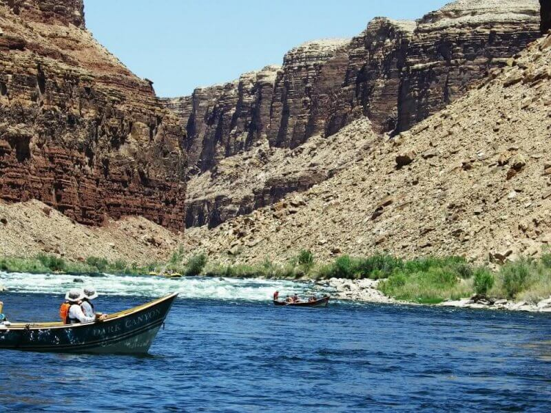 wooden boats going through small rapids on river rafting trip through grand canyon