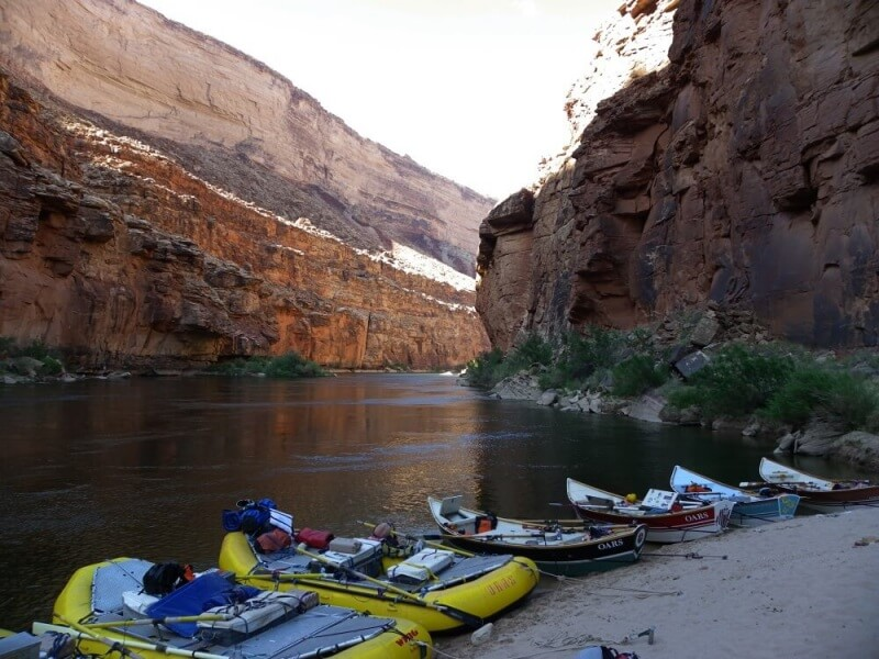 rafts and doreis pulled up on beach inside grand canyon on river rafting trip through grand canyon