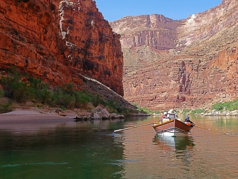 small wooden boat surrounded by large canyon on river rafting trip through grand canyon