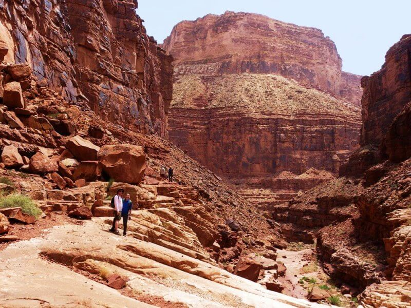 two people surrounded by grand canyon on river rafting trip through Grand Canyon