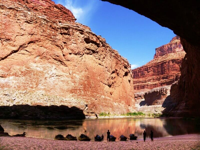 boats and rafts drawn up on beach inside large cavern looking out at canyon walls and river on river trip through grand canyon