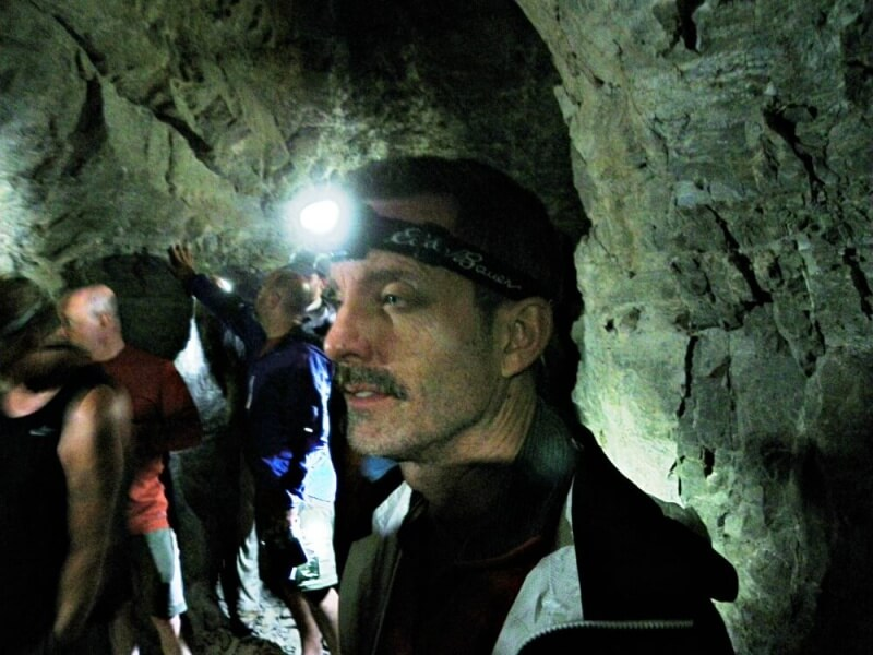 man in mine with headlamp inside abandoned tunnel in grand canyon on river trip through grand canyon