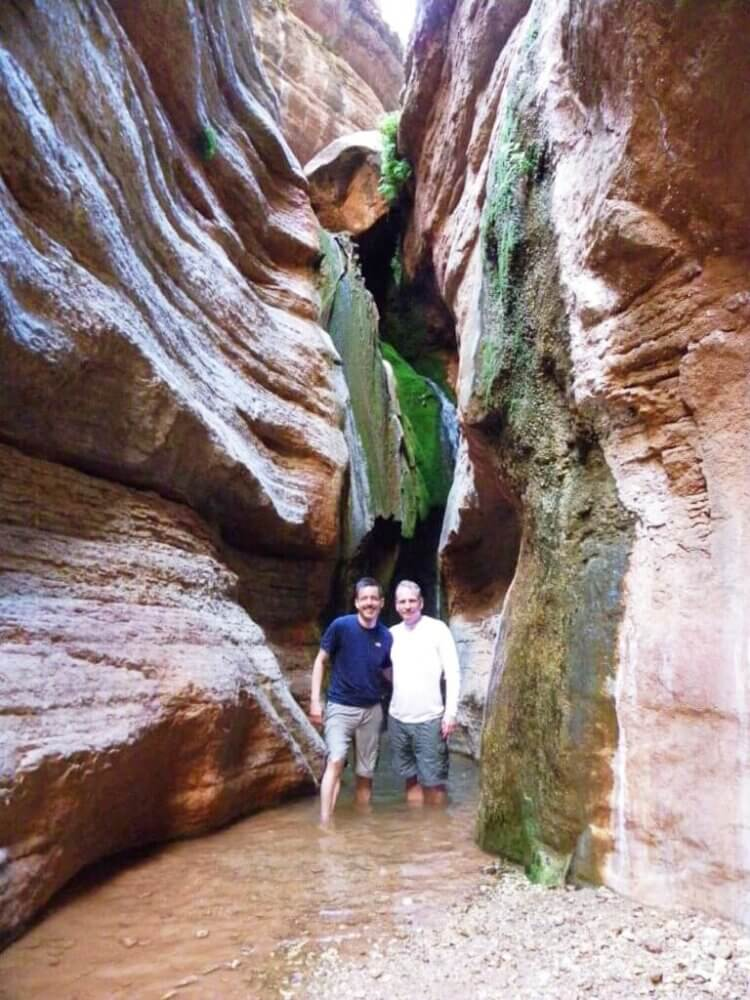 two men standing shin deep in water surrounded by walls of canyon on each side very narrow on river trip through grand canyon