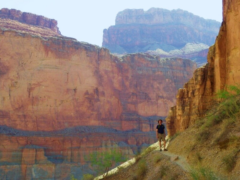 man hiking on narrow path on side of cliff with canyon walls behind him on river trip through grand canyon