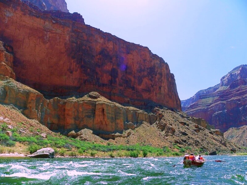 small wooden boat going through rapids in grand canyon on river rafting trip through grand canyon