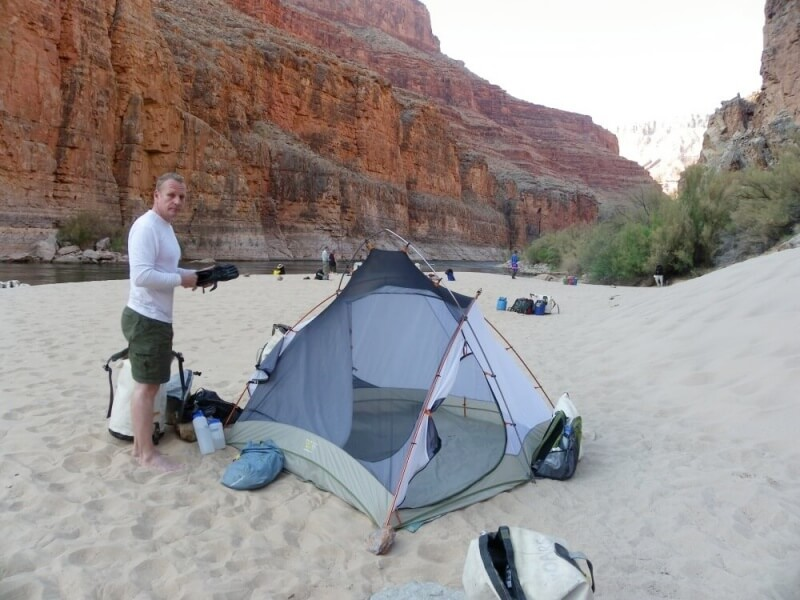 man standing next to tent on beach inside grand canyon on river rafting trip through grand canyon
