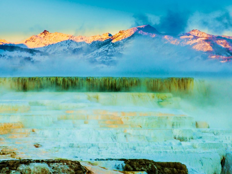 Yellowstone Winter Mommoth Hot Springs travertine terraces with snowy mountains behind them